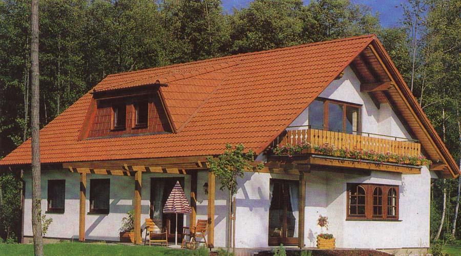 Фото дома с мансардной крышей и балконом.